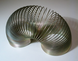 The slinky represents the continuous, open life process moving unidirectionally from conception to death in a non-linear plane.